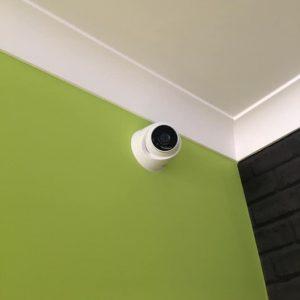 Fixed turret camera on green wall