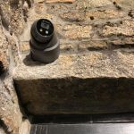 Security camera fixed to stone wall